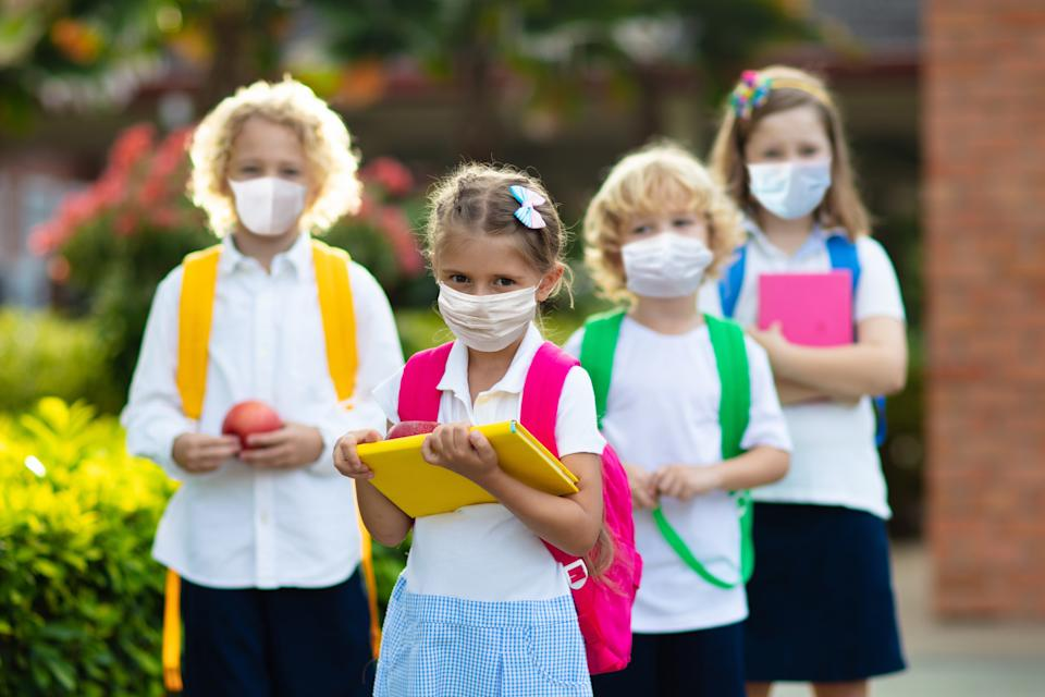 School child wearing face mask during corona virus and flu outbreak. Boy and girl going back to school after covid-19 quarantine and lockdown. Group of kids in masks for coronavirus prevention.