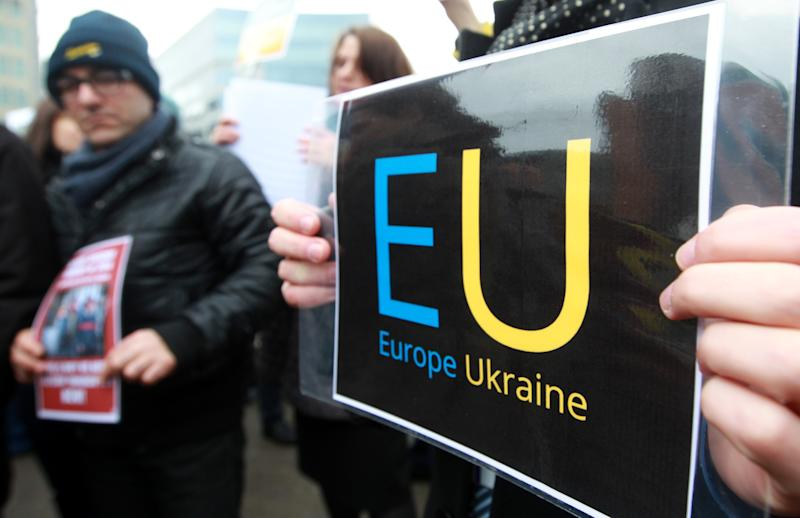 Ukrainian protesters stand outside the European Council building in Brussels, Thursday, Feb. 20, 2014. The 28-nation European Union is holding an emergency meeting on Ukraine, to consider sanctions against those behind the violence. (AP Photo/Yves Logghe)
