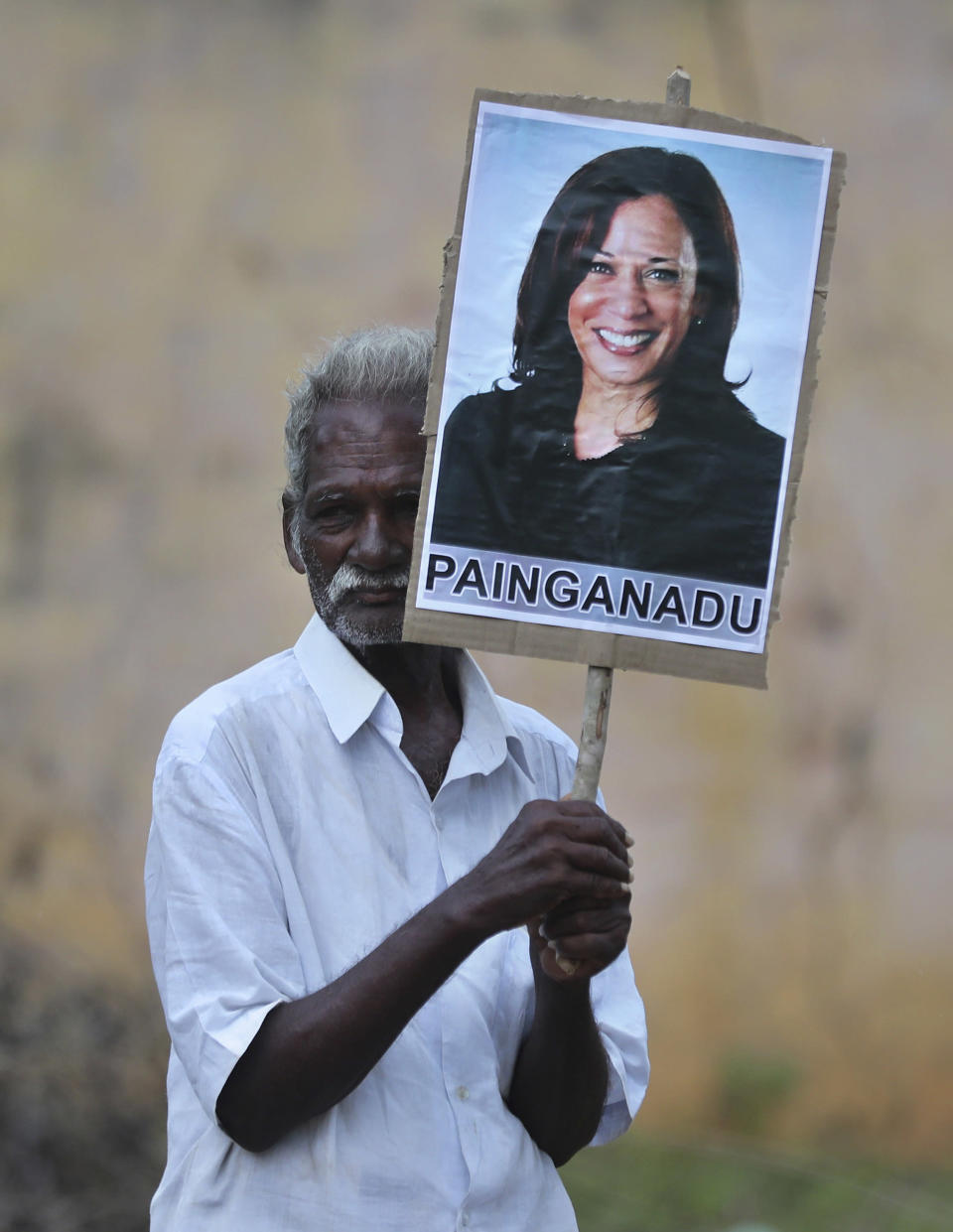 An elderly villager holds a placard of U.S. Vice President-elect Kamala Harris during celebrations for her victory in Painganadu a neighboring village of Thulasendrapuram, the hometown of Harris' maternal grandfather, south of Chennai, Tamil Nadu state, India, Sunday, Nov. 8, 2020. Waking up to the news of Kamala Harris' election as Joe Biden's running mate, overjoyed people in her Indian grandfather's hometown are setting off firecrackers, carrying her placards and offering prayers. (AP Photo/Aijaz Rahi)