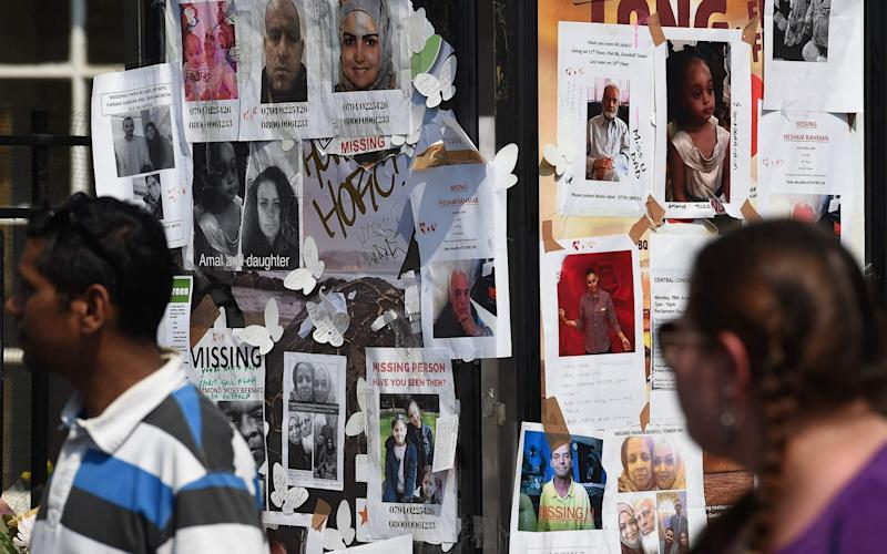 People pass posters showing images of missing people, in Kensington, west London - Credit: PAUL ELLIS/AFP/Getty Images
