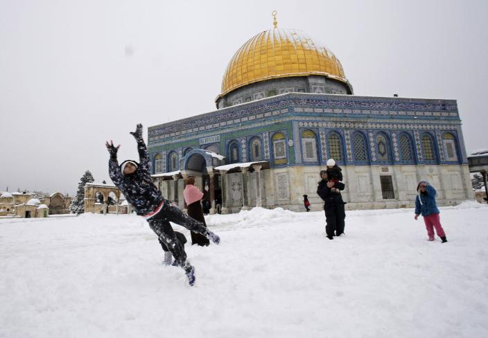 Children play in the snow in front of the Dome of the Rock on the compound known to Muslims as Noble Sanctuary and to Jews as Temple Mount, in Jerusalem's Old City February 20, 2015. Snow covered Jerusalem and mountainous areas of Israel early Friday morning and the education ministry closed schools for the day. (REUTERS/Ammar Awad)