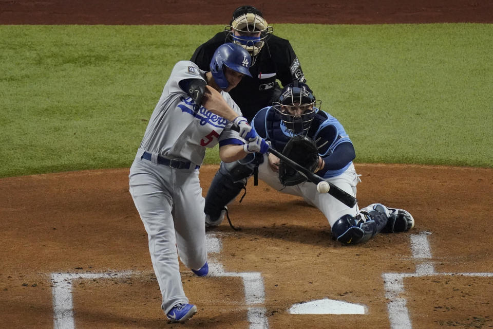 Los Angeles Dodgers' Corey Seager hits a RBI-single against the Tampa Bay Rays during the first inning in Game 5 of the baseball World Series Sunday, Oct. 25, 2020, in Arlington, Texas. (AP Photo/Sue Ogrocki)