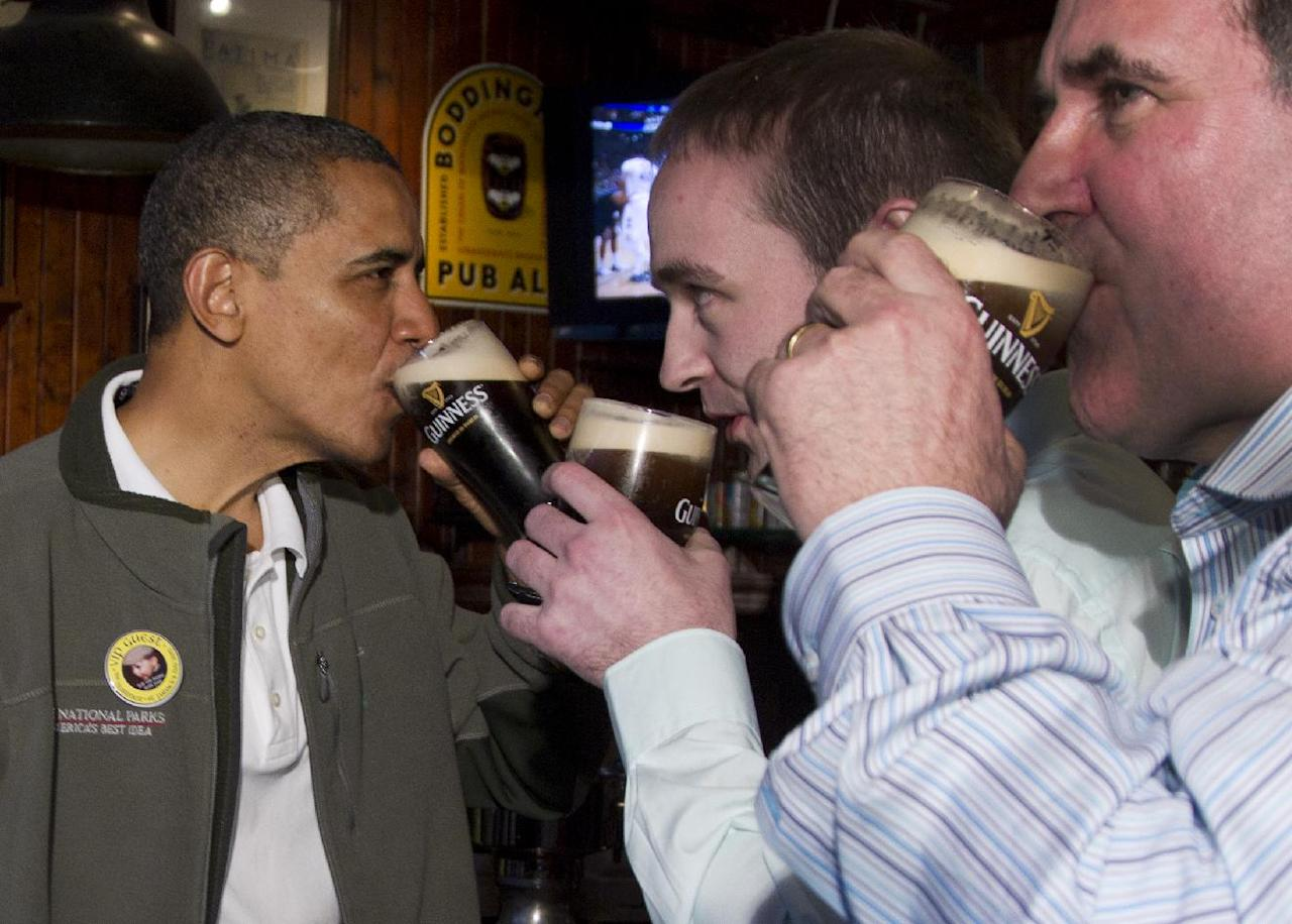 President Barack Obama drinks a Guinness with his ancestral cousin from Moneygall Ireland Henry Healy, center, and the owner of the pub in Moneygall Ireland, Ollie Hayes, right, at The Dubliner Restaurant and Pub and Restaurant on St. Patrick's Day, Saturday, March 17, 2012, in Washington. (AP Photo/Carolyn Kaster)