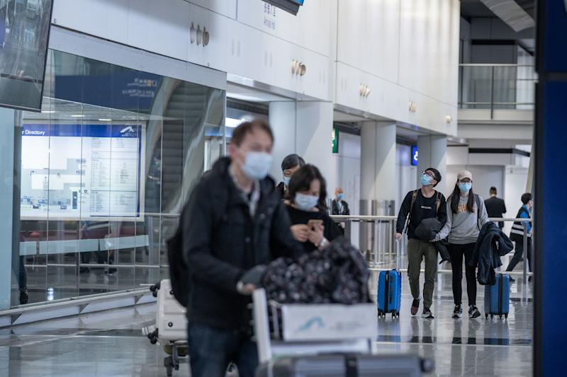 Travelers seen wearing surgical masks as a protective measure from the deadly coronavirus as they exit the arrival hall area at Hong Kong international airport. Hundreds of flights between mainland Chinese cities and Hong Kong cancel as the 14 days mandatory quarantine measure which travelers will have to stay at home or hotel to be quarantined takes into effect. (Photo by Geovien So / SOPA Images/Sipa USA)