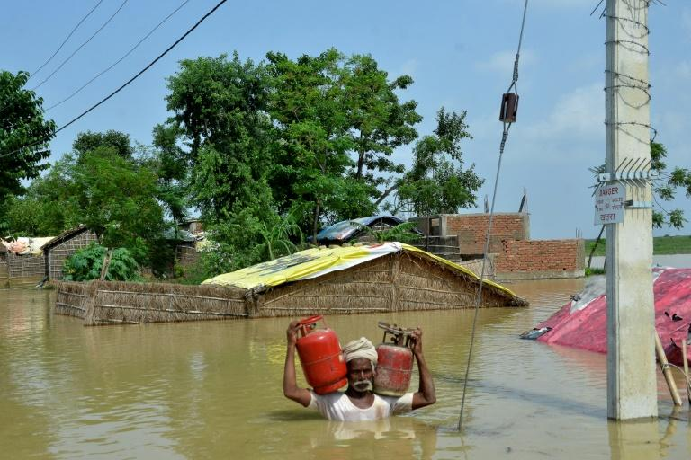 A resident of Muzaffarpur carries gas canisters from his flooded home following heavy monsoon rains in the Indian state of Bihar (AFP Photo/STR)