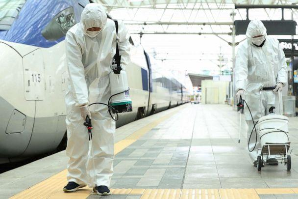 PHOTO: Railway workers wearing protective gear spray disinfectant, as part of preventive measures against the spread of the novel coronavirus, at a railway station in Seoul, South Korea, on February 25, 2020. (-/YONHAP/AFP via Getty Images)