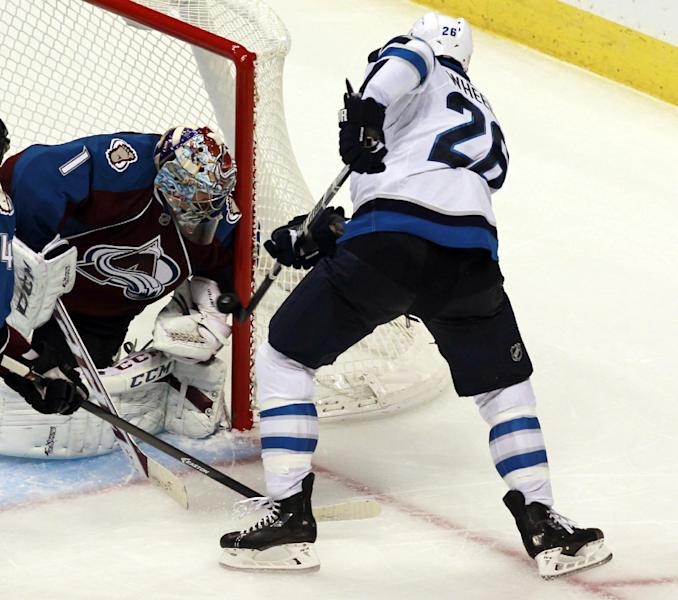 Colorado Avalanche goalie Semyon Varlamov, left, of Russia, stops a shot off the stick of Winnipeg Jets right wing Blake Wheeler in the third period of the Avalanche's 3-2 victory in an NHL hockey game in Denver on Sunday, Oct. 27, 2013. (AP Photo/David Zalubowski)