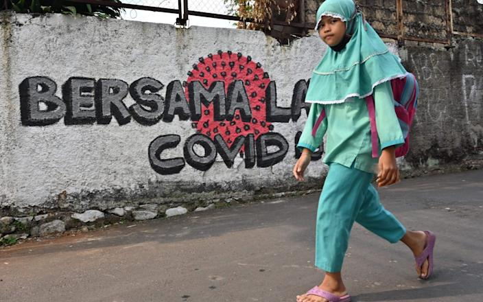 """An Indonesian girl walks past a sign that says """"together against Covid"""" - Adek Berry/AFP"""