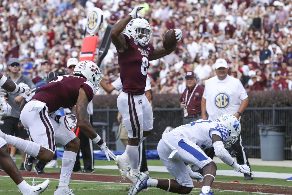 Mississippi State running back Kylin Hill (8) leaps over a Kentucky defender to score a touchdown during the first half of an NCAA college football game, Saturday, Sept. 21, 2019, in Starkville, Miss. (AP Photo/Kelly Donoho)
