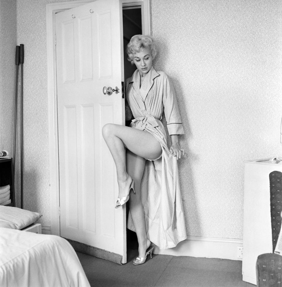 Lesley wears a robe while standing in a door frame, circa 1964.