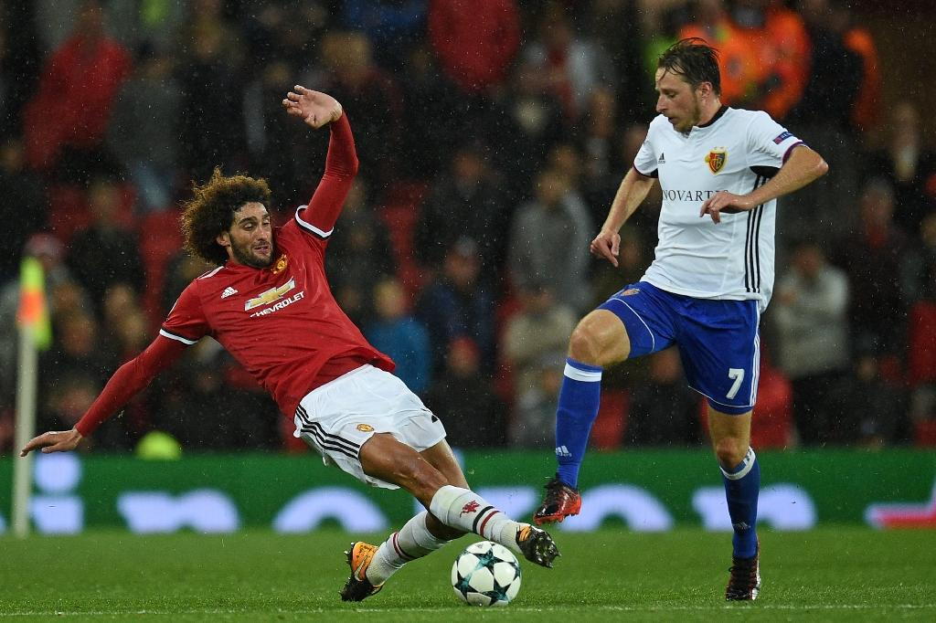 Manchester United midfielder Marouane Fellaini (L) tackles Basel midfielder Luca Zuffi during the Champions League Group A match at Old trafford in Manchester on September 12, 2017 (AFP Photo/Oli SCARFF                          )