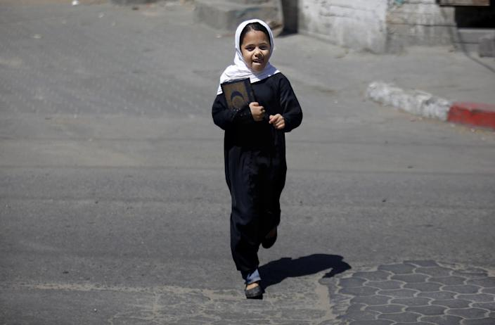 A Palestinian Muslim Sunni girl holds a copy of the Quran, making her way to al-Sahab mosque in Gaza City, Sunday, June 23, 2013. Hatreds between Shiites and Sunnis are now more virulent than ever in the Arab world because of Syria's brutal civil war. Hard-line clerics and politicians on both sides have added fuel, depicting the fight as essentially a war of survival for their sect. (AP Photo/Hatem Moussa)