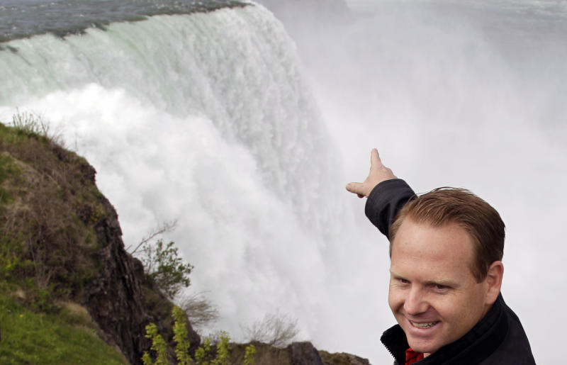 Nik Wallenda points to Niagara Falls after a news conference in Niagara Falls, N.Y., Wednesday, May 2, 2012.  Wallenda will try to cross the Niagara Gorge on a tightrope June 15. The seventh-generation member of the Flying Wallendas spent months getting the necessary permissions from Canada and the United States for the cross-border stunt. (AP Photo/David Duprey)