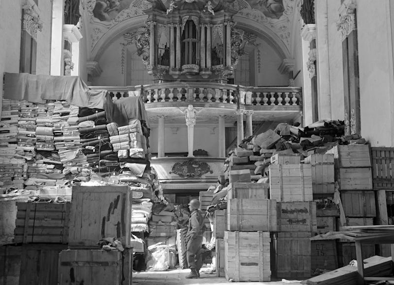 In this April 24, 1945 photo released by the U.S. National Archives, an American soldier stands among German loot stored in a church at Elligen, Germany. Holocaust survivors and their relatives, as well as art collectors and museums, can go online beginning Monday, Oct. 18, 2010 to search a historical database of more than 20,000 art objects stolen in German-occupied France and Belgium from 1940 to 1944. (AP Photo/U.S. National Archives)