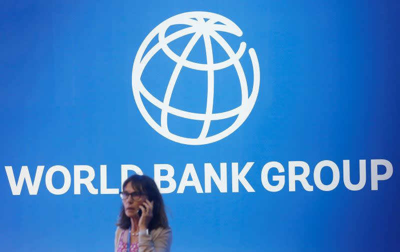 FILE PHOTO: A participant stands near a logo of World Bank at the International Monetary Fund - World Bank Annual Meeting 2018 in Nusa Dua