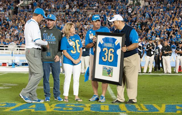 PASADENA, CA - SEPTEMBER 21: (L-R) Head Coach Jim Mora Jr. of the UCLA Bruins honors the memory of Nick Pasquale #36 with his brother A.J Pasquale, mother Laurie Pasquale, father Mel Pasquale and UCLA Athletic Director Dan Guerrero during the first quarter break against the New Mexico State Aggies at the Rose Bowl on September 21, 2013 in Pasadena, California. (Photo by Don Liebig-Pool/Getty Images)
