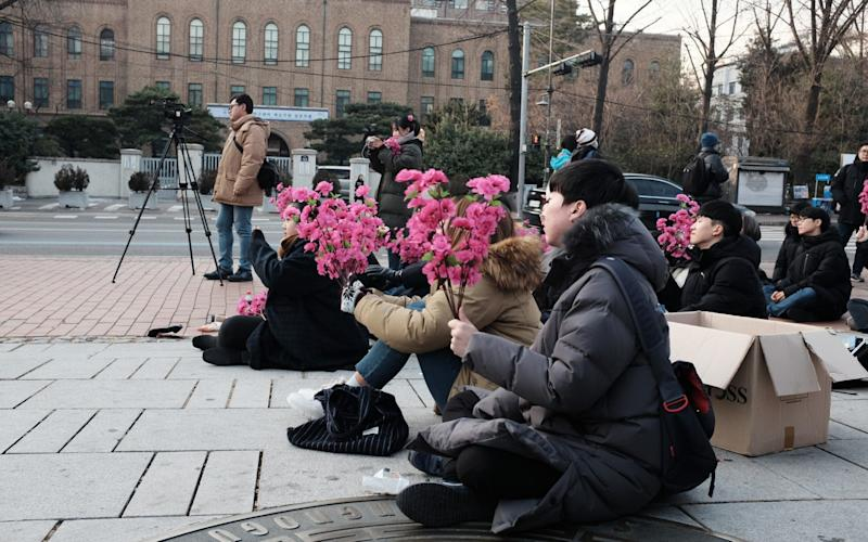 South Korean students gather with bouquets of rosebays to plan for Kim Jong-un's trip to Seoul - Junho Lee