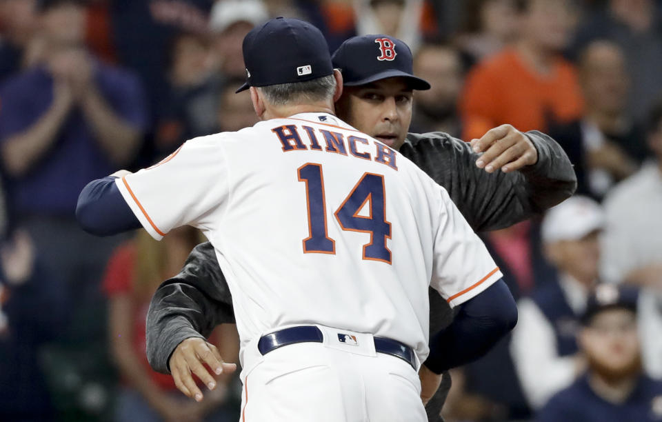 Houston Astros manager AJ Hinch, left, and Boston Red Sox manager Alex Cora hug before Game 3 of a baseball American League Championship Series on Tuesday, Oct. 16, 2018, in Houston. (AP Photo/David J. Phillip)