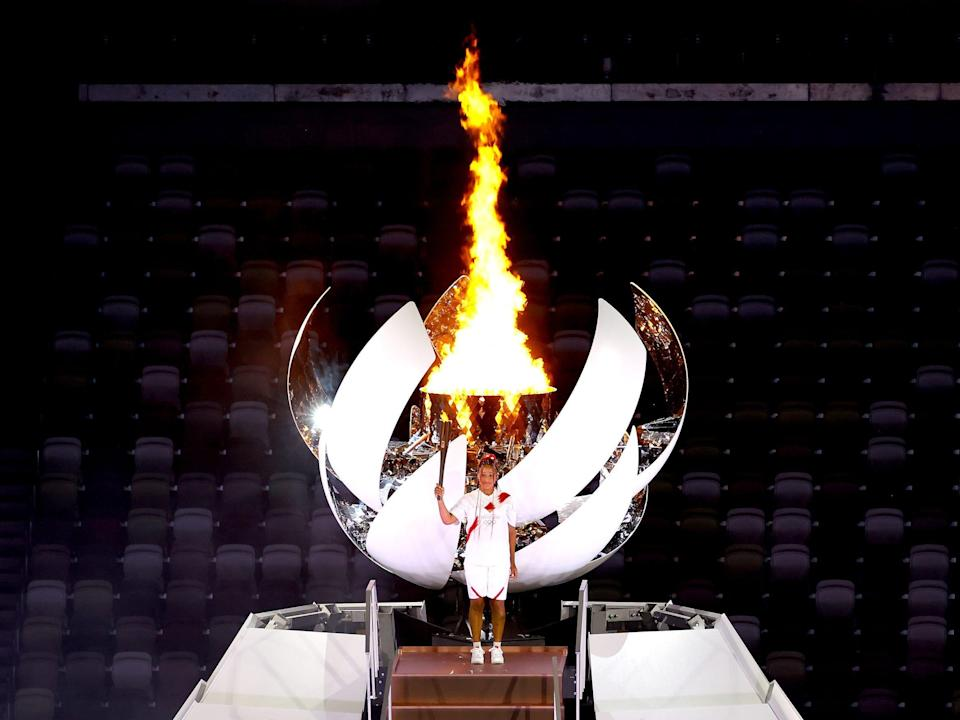 Naomi Osaka of Team Japan lights the Olympic cauldron with the Olympic torch during the opening ceremony at an empty Olympic Stadium.