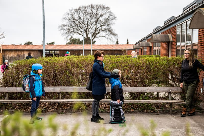 Parents with their children stand in a queue waiting to get inside Stengaard School following the coronavirus disease (COVID-19) outbreak in  all schools north of Copenhagen