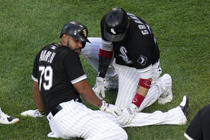 Chicago White Sox's Jose Abreu sits on the ground near home plate as Yasmani Grandal looks at his left knee after Abreu ended up on the ground after Jake Lamb scored during the first inning of a baseball game against the Toronto Blue Jays Wednesday, June 9, 2021, in Chicago. Abreu stayed in the game. (AP Photo/Charles Rex Arbogast)