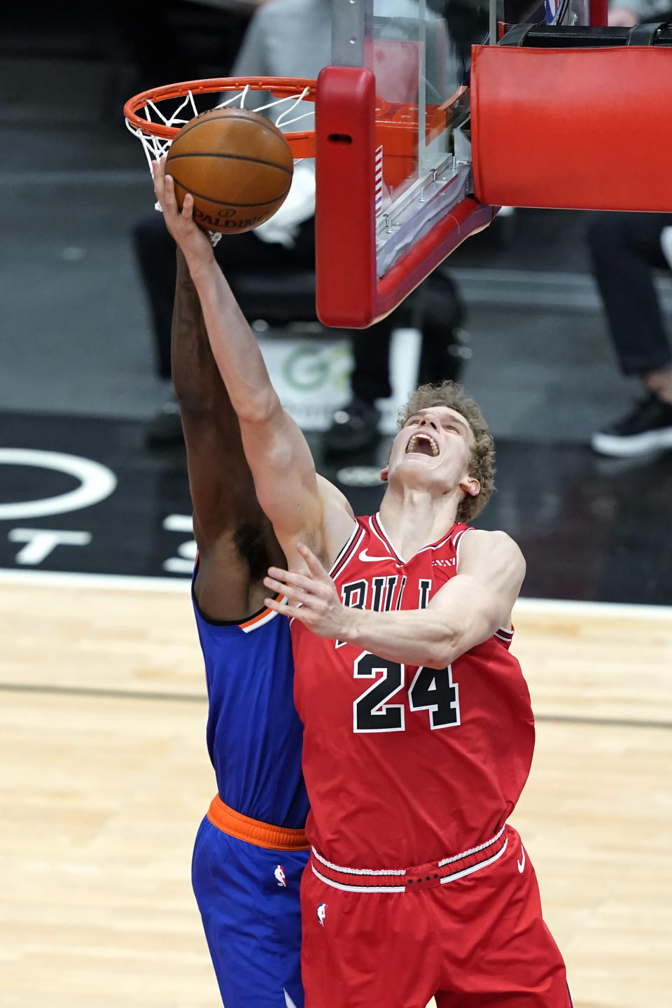 Chicago Bulls' Lauri Markkanen (24) scores on a reverse layup past New York Knicks' Julius Randle during the first half of an NBA basketball game Monday, Feb. 1, 2021, in Chicago. (AP Photo/Charles Rex Arbogast)