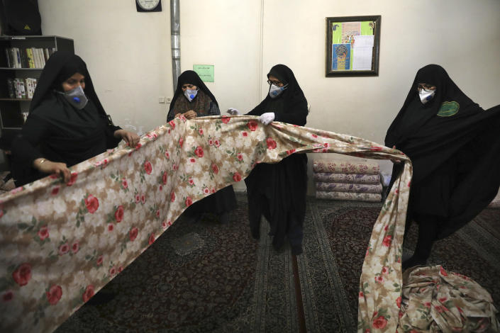 Volunteer women wearing face masks to curb the spread of the new coronavirus prepare fabric to sew bed sheets for hospitals, in a mosque in southern Tehran, Iran, Sunday, April 5, 2020. Iran is battling the worst new coronavirus outbreak in the Mideast. (AP Photo/Vahid Salemi)