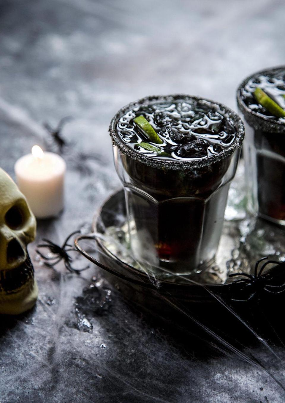 """<p>Turn a classic margarita into a ghoulish drink by adding red, blue, and green food coloring. The deep black color is easy to achieve—and so spooky!</p><p><strong>Get the recipe at <a href=""""https://www.climbinggriermountain.com/2018/10/hallow-rita-halloween-margarita.html"""" rel=""""nofollow noopener"""" target=""""_blank"""" data-ylk=""""slk:Climbing Grier Mountain"""" class=""""link rapid-noclick-resp"""">Climbing Grier Mountain</a>. </strong></p><p><a class=""""link rapid-noclick-resp"""" href=""""https://go.redirectingat.com?id=74968X1596630&url=https%3A%2F%2Fwww.walmart.com%2Fsearch%2F%3Fquery%3Dpioneer%2Bwoman%2Bserving%2Btrays&sref=https%3A%2F%2Fwww.thepioneerwoman.com%2Fholidays-celebrations%2Fg36982659%2Fhalloween-drink-recipes%2F"""" rel=""""nofollow noopener"""" target=""""_blank"""" data-ylk=""""slk:SHOP SERVING TRAYS"""">SHOP SERVING TRAYS</a></p>"""
