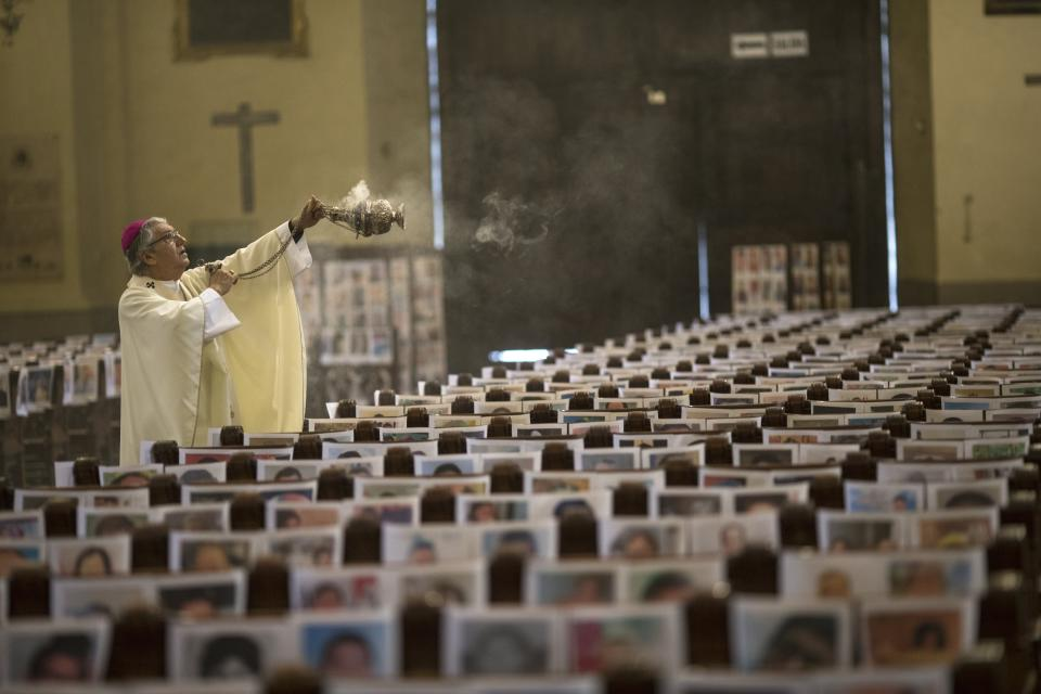 The Archbishop of Lima Carlos Castillo swings a censer over several of the more than 4 thousand portraits of COVID-19 victims during the Corpus Christi Mass at the Cathedral of Lima, Peru, Sunday, June 14, 2020. (AP Photo/Rodrigo Abd)