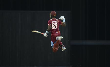 West Indies' Darren Sammy leaps to celebrate after the West Indies won their second T20 international cricket match against England at Kensington Oval in Bridgetown, Barbados March 11, 2014. REUTERS/Philip Brown