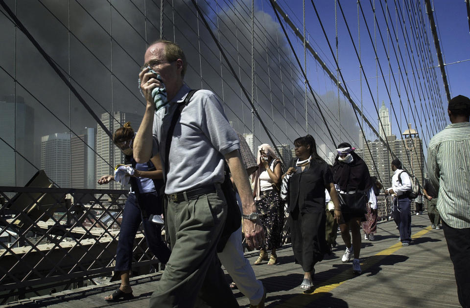 <p>People walk over New York's Brooklyn Bridge from Manhattan to Brooklyn following the collapse of both World Trade Center towers on Sept. 11, 2001. (AP Photo/Mark Lennihan)</p>