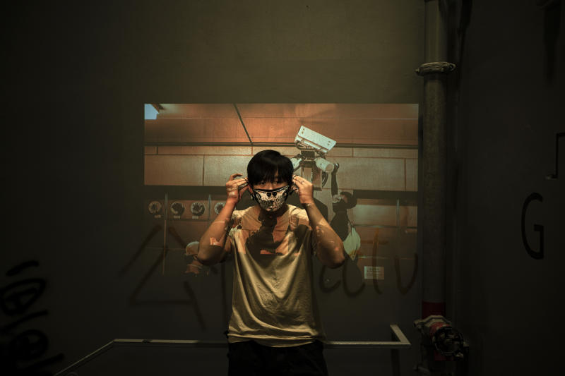 A protester who identified himself as Jason, poses for a portrait as a projector displays a photograph, previously taken during the unrest, over him at a protest in Hong Kong. In smashing, spray-painting and shining lasers on surveillance cameras across the semi-autonomous Chinese city, these demonstrators say they are fighting back against an omniscient state security apparatus that already envelops mainland China. (Photo: Felipe Dana/AP)