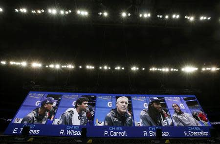 Seattle Seahawks head coach Pete Carroll (C) is shown on a video monitor with (L to R) Earl Thomas, quarterback Russell Wilson, cornerback Richard Sherman and strong safety Kam Chancellor during Media Day for Super Bowl XLVIII at the Prudential Center in Newark, New Jersey January 28, 2014. REUTERS/Shannon Stapleton