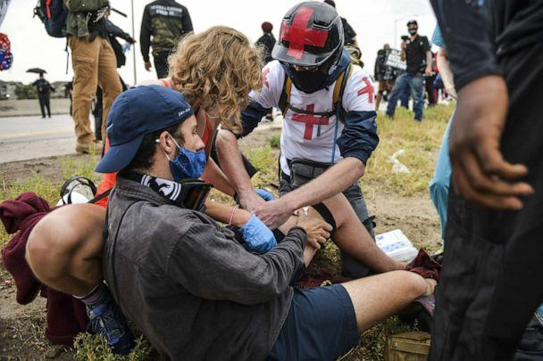 PHOTO: People help a man who was shot after a car sped through a crowd of protestors marching on I-225 to protest the death of Elijah McClain on July 25, 2020 in Aurora, Colorado. (Michael Ciaglo/Getty Images)