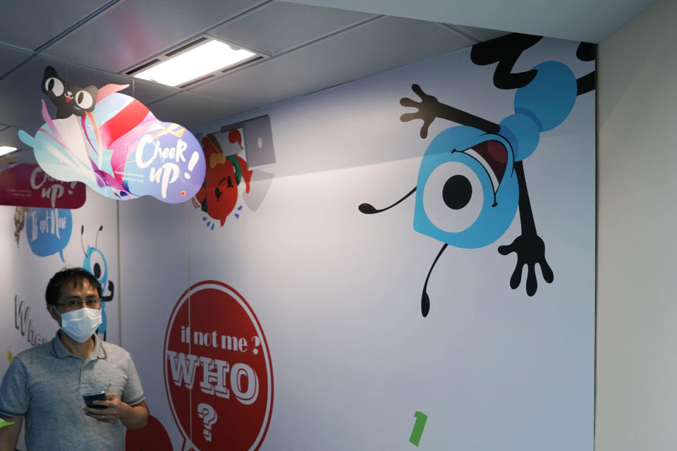 In this Friday, Oct. 23, 2020 photo, an employee walks past the picture of Ant Group's mascot at the Ant Group office in Hong Kong. China's Ant Group will try to raise nearly $35 billion in its initial public offering in Shanghai and Hong Kong, which would make it the largest share offering in history. Alibaba-affiliated Ant Group, which operates a suite of financial products including the widely-used Alipay digital wallet in China and one of the world's largest money market funds, will hold dual listings in Shanghai and Hong Kong. (AP Photo/Kin Cheung)