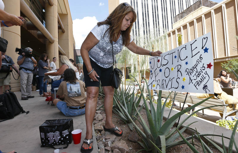 Carol Peifer, of Glendale, Ariz., places a sign in front of Maricopa County Superior Court as she and dozens of other spectators wait for a verdict in the Jodi Arias murder trial, Tuesday, May 7, 2013, in Phoenix. A Phoenix jury is on its third day of deliberations in the trial of Jodi Arias, who is accused of murdering her one-time boyfriend Travis Alexander, in Arizona. (AP Photo/Ross D. Franklin)