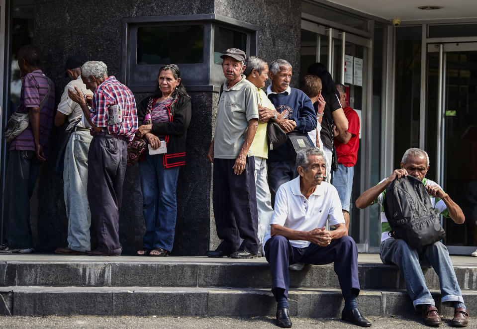 Elderly people wait for their pension monthly payment outside a bank in Caracas, on February 22, 2019. (Photo by RONALDO SCHEMIDT / AFP)        (Photo credit should read RONALDO SCHEMIDT/AFP via Getty Images)