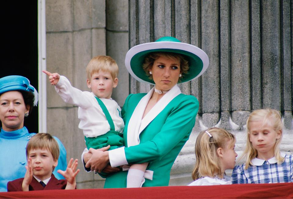UNITED KINGDOM - JUNE 11:  Diana, Princess of Wales, holding a young Prince Harry in her arms as she watches Trooping the Colour with Prince William, Lady Rose Windsor, Lady Davina Windsor and Princess Margaret from the balcony of Buckingham Palace  (Photo by Tim Graham Photo Library via Getty Images)