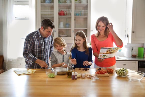 A family of four happily piecing together a Blue Apron meal kit.