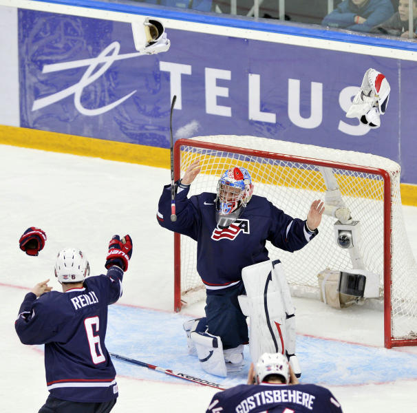 Team USA goalie John Gibson, center, celebrates with teammates Mike Reilly, left, and Shayne Gostisbehere after defeating Sweden 3-1 in the gold medal hockey game at the IIHF World Junior ice hockey championships in Ufa, Russia, on Saturday, Jan. 5, 2013. (AP Photo/The Canadian Press, Nathan Denette)