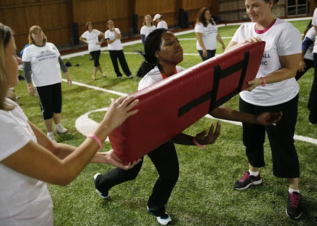 Participants including Jennifer Roebuck, of Richton Park, Ill., receive instruction on how to safely tackle during a safety clinic hosted by the NFL and the Chicago Bears for the mothers of youth football players on Tuesday, Oct. 29, 2013, at Halas Hall in Lake Forest, Ill. (AP Photo/Andrew A. Nelles)