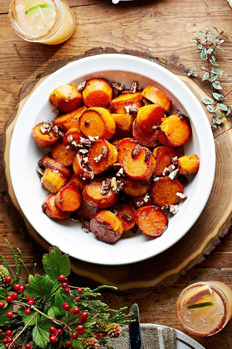 """<p>Store-bought candied or spiced pecans add crunch to this comfort food dish. To make ahead, cover and chill cooked potatoes in glaze in baking dishes the day before. Let stand at room temperature, then reheat covered at 350 degrees F for about 20 minutes or until thoroughly heated.</p><p><strong><a href=""""https://www.countryliving.com/food-drinks/recipes/a5913/sorghum-sweet-potatoes-recipe-clx1114/"""" rel=""""nofollow noopener"""" target=""""_blank"""" data-ylk=""""slk:Get the recipe"""" class=""""link rapid-noclick-resp"""">Get the recipe</a>.</strong></p>"""