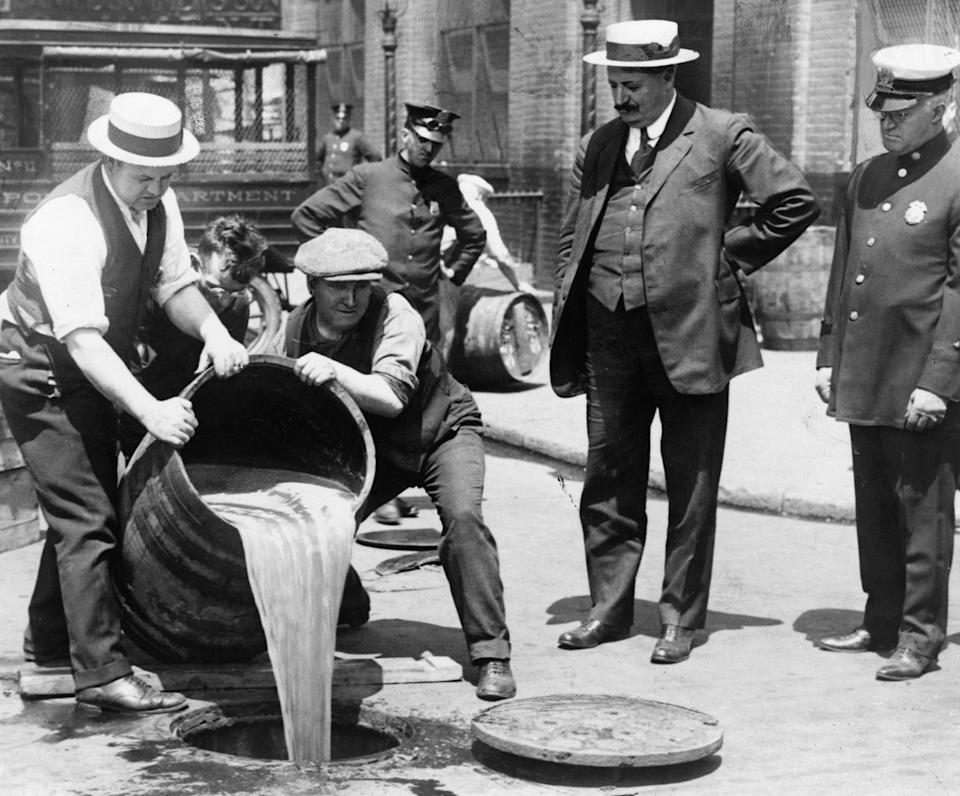 Deputy Police Commissioner John A. Leach (right) watches as two men pour liquor into the sewer, following a Prohibition-prompted raid. Congress passed the 18th Amendment in 1920, banning the manufacturing and sale of alcohol and ushering in the 13-year period of Prohibition (the era ended with the passing of the 21st Amendment in 1933).