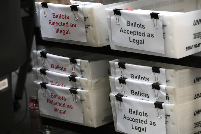 FILE - In this July 30, 2020, file photo, boxes for illegal and legal vote-by-mail ballots are shown as the the Miami-Dade County canvassing board meets to verify signatures on vote-by-mail ballots for the Aug. 18 primary election at the Miami-Dade County Elections Department in Doral, Fla. Never in U.S. history will so many people exercise the right on which their democracy hinges by marking a ballot at home. (AP Photo/Lynne Sladky, File)