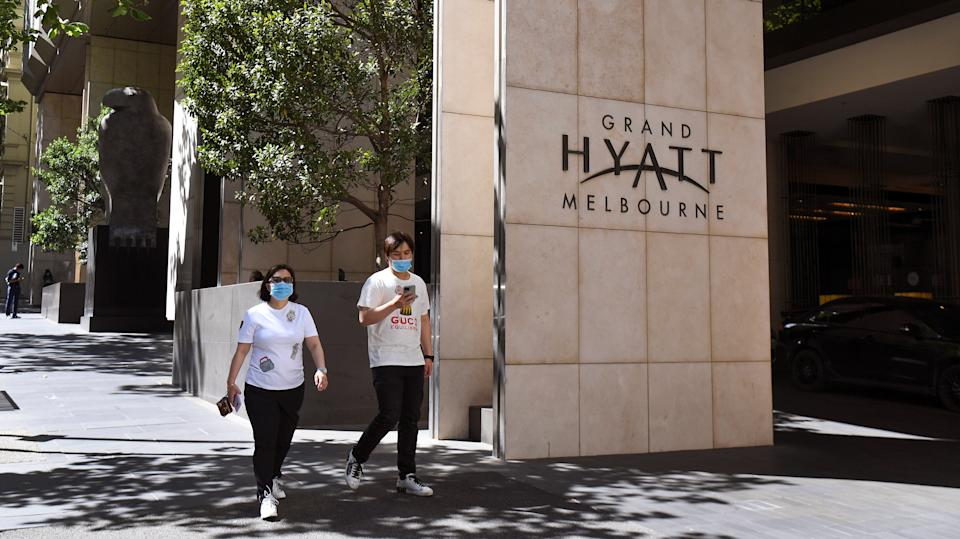 People walk past the Grand Hyatt hotel which will host tennis players and officials in Melbourne on January 14, 2021, as they quarantine ahead of the Australian Open tennis tournament.