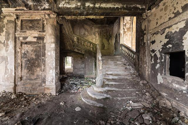 <p>Eerie photographs reveal the abandoned burned-down parliament building where 500 people were killed in the Sukhumi massacre. More than two decades since the conflict, the site remains a visual scar and a reminder of Abkhazia's battle for independence from Georgia. (Photo: Bob Thissen/Caters News) </p>