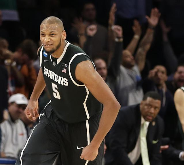 Michigan State's Adreian Payne celebrates after scoring in the second half of a regional semifinal against Virginia at the NCAA men's college basketball tournament, early Saturday, March 29, 2014, in New York. Michigan State won 61-59. (AP Photo/Seth Wenig)