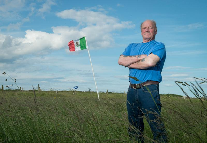 Michael Forbes poses for a photograph beside the Mexican flag he erected alongside Donald Trump's International Golf Links course, north of Aberdeen on the East coast of Scotland, on June 21, 2016. Trump is heading to Scotland to relaunch his Turnberry golf course and hotel in southwest Scotland following a £200 million ($300 million, 260 million euro) revamp of the resort, and the property tycoon will also visit his Balmedie course. Another Mexican flag is being flown at the nearby home of Michael Forbes, who refused to sell his land to Trump before the course opened. / AFP / Michal Wachucik (Photo credit should read MICHAL WACHUCIK/AFP via Getty Images)
