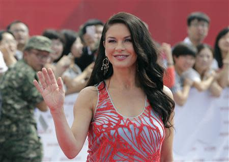 British actress Catherine Zeta-Jones waves to fans as she arrives for the launch ceremony of the Qingdao Oriental Movie Metropolis on the outskirts of Qingdao, Shandong province September 22, 2013. REUTERS/Jason Lee