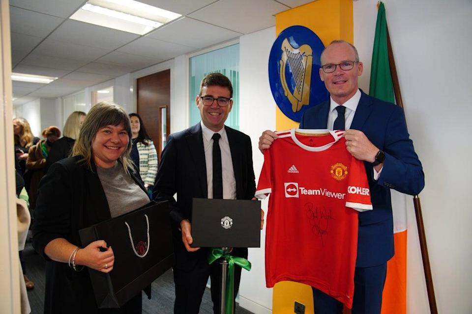 Foreign Affairs Minister Simon Coveney being presented with a signed Denis Irwin Manchester United FC shirt by Stockport Council Leader Elise Wilson and mayor of Greater Manchester, Andy Burnham, in Manchester, at the official opening of the Consulate General of Ireland for the North of England (Peter Byrne/PA) (PA Wire)